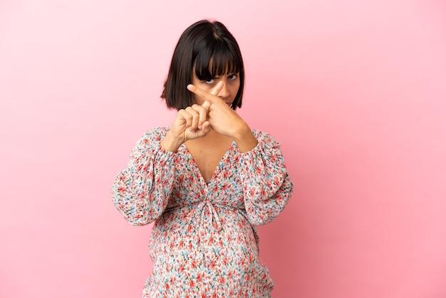 Młoda kobieta w ciąży na odosobnionym różowym tle, wykonując gest zatrzymania ręką, aby zatrzymać akt