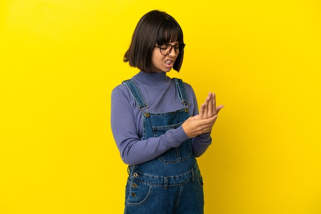 Młoda kobieta w ciąży na odosobnionym żółtym tle cierpi na ból w rękach