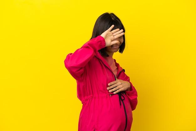 Młoda kobieta w ciąży na odosobnionym żółtym tle nerwowe rozciąganie rąk do przodu