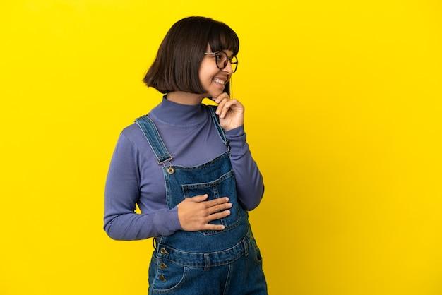 Młoda kobieta w ciąży na odosobnionym żółtym tle, patrząc w bok i uśmiechając się