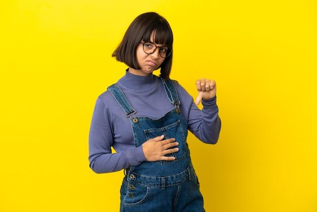 Młoda kobieta w ciąży na odosobnionym żółtym tle pokazując kciuk w dół z negatywną ekspresją