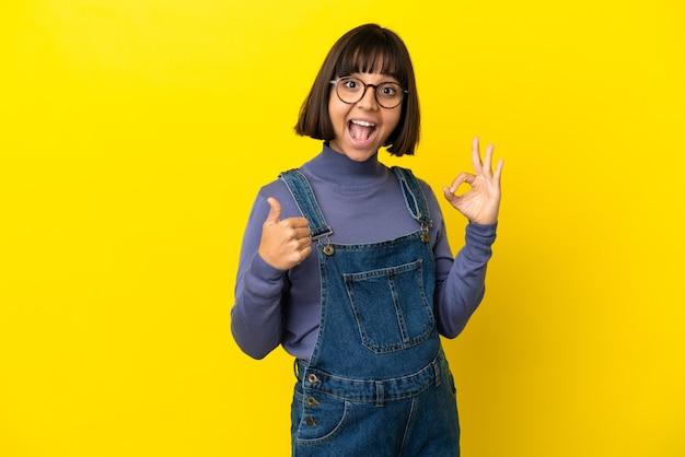 Młoda kobieta w ciąży na odosobnionym żółtym tle pokazując znak ok i gest kciuka w górę
