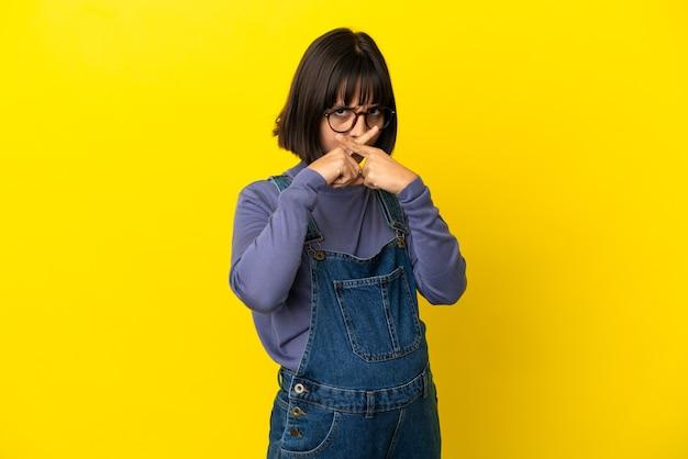 Młoda kobieta w ciąży na odosobnionym żółtym tle pokazującym znak gestu ciszy