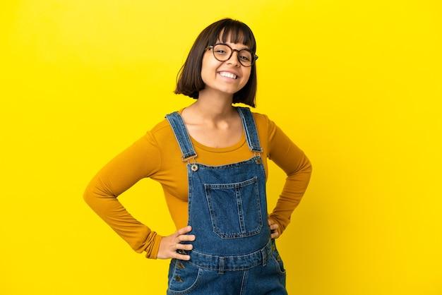 Młoda kobieta w ciąży na odosobnionym żółtym tle pozuje z rękami na biodrach i uśmiecha się
