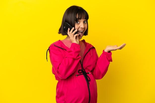 Młoda kobieta w ciąży na odosobnionym żółtym tle, prowadząca rozmowę z telefonem komórkowym z kimś