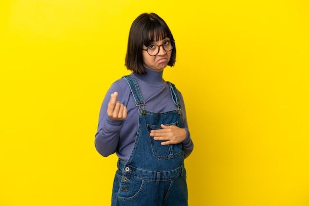 Młoda kobieta w ciąży na odosobnionym żółtym tle robi pieniądze gest