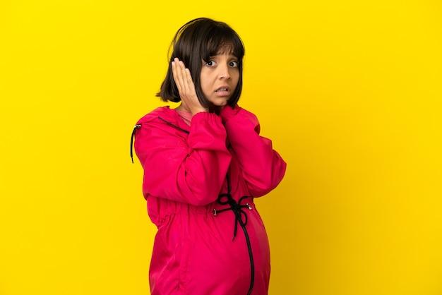 Młoda kobieta w ciąży na odosobnionym żółtym tle sfrustrowana i zakrywająca uszy