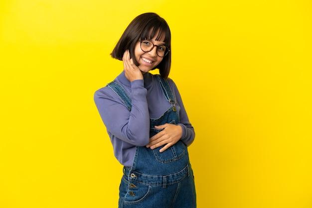 Młoda kobieta w ciąży na odosobnionym żółtym tle śmiejąc się