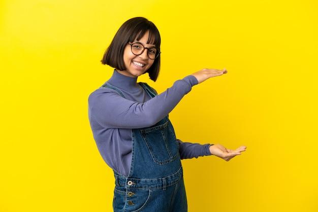 Młoda kobieta w ciąży na odosobnionym żółtym tle trzyma copyspace, aby wstawić reklamę