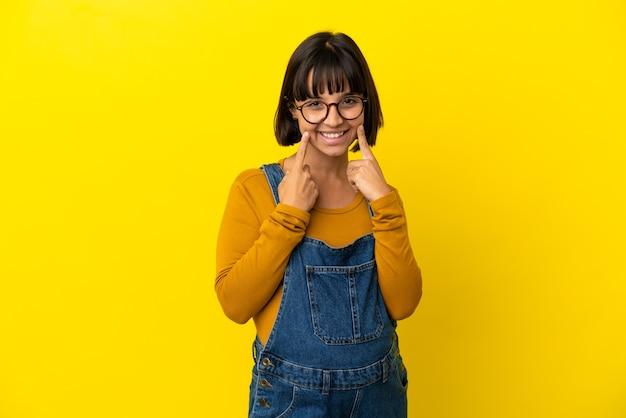 Młoda kobieta w ciąży na odosobnionym żółtym tle uśmiecha się ze szczęśliwym i przyjemnym wyrazem twarzy