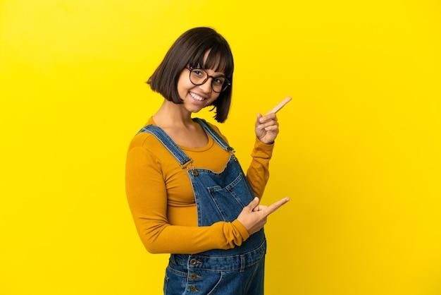 Młoda kobieta w ciąży na odosobnionym żółtym tle, wskazując palcem na bok i przedstawiająca produkt