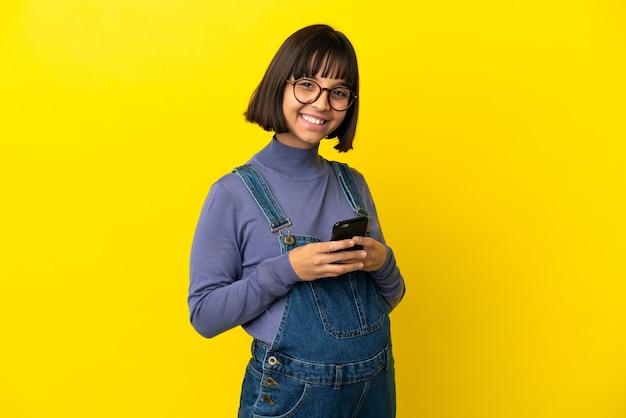 Młoda kobieta w ciąży na odosobnionym żółtym tle wysyła wiadomość za pomocą telefonu komórkowego