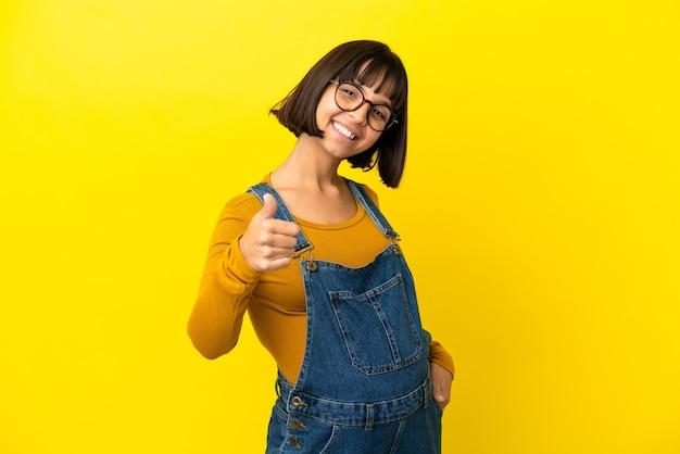 Młoda kobieta w ciąży na odosobnionym żółtym tle z kciukami do góry, ponieważ wydarzyło się coś dobrego
