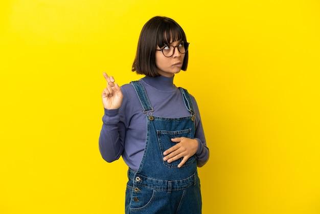 Młoda kobieta w ciąży na odosobnionym żółtym tle z palcami krzyżującymi i życzącymi wszystkiego najlepszego