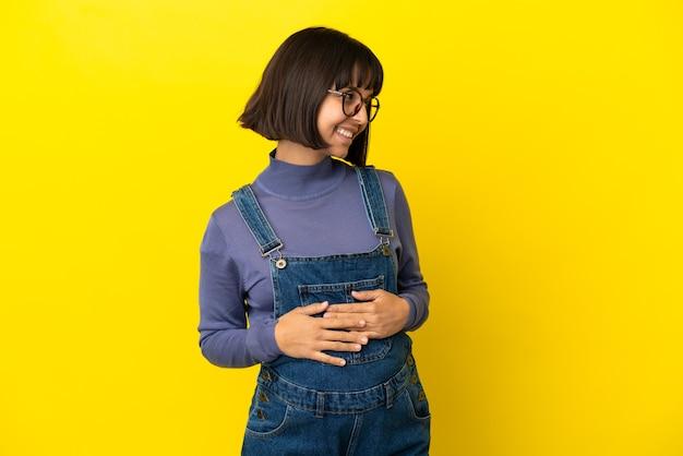 Młoda kobieta w ciąży na odosobnionym żółtym tle z rękami skrzyżowanymi i szczęśliwymi