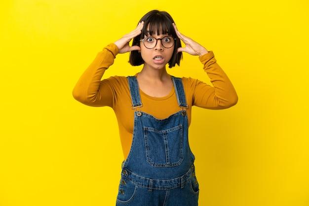 Młoda kobieta w ciąży na odosobnionym żółtym tle z wyrazem zaskoczenia