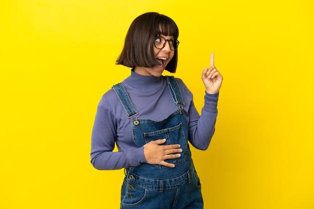 Młoda kobieta w ciąży na odosobnionym żółtym tle, zamierzająca zrealizować rozwiązanie, podnosząc palec w górę