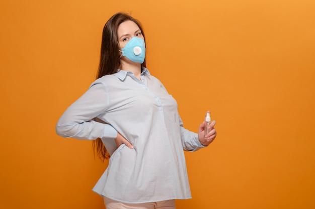 Młoda kobieta w ciąży na ścianie pomarańczowy w ochronnej maski medyczne i spray antyseptyczne w ręku