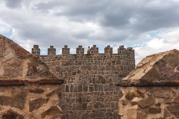 Młoda kobieta w ciąży na szczycie średniowiecznej wieży murów miejskich avila, hiszpania.