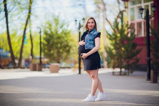 Młoda kobieta w ciąży na tle budynku mieszkalnego