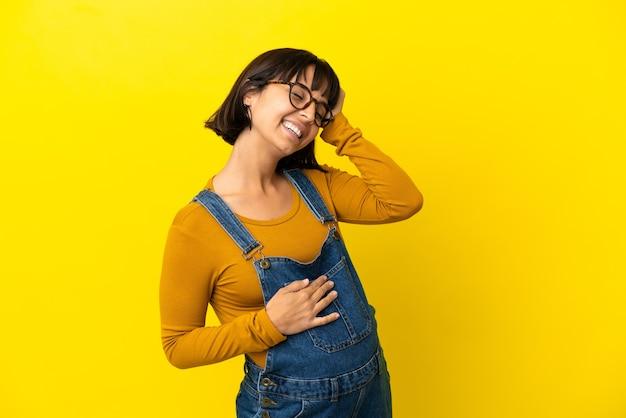 Młoda kobieta w ciąży nad odizolowaną żółtą powierzchnią uświadomiła sobie coś i zamierza znaleźć rozwiązanie