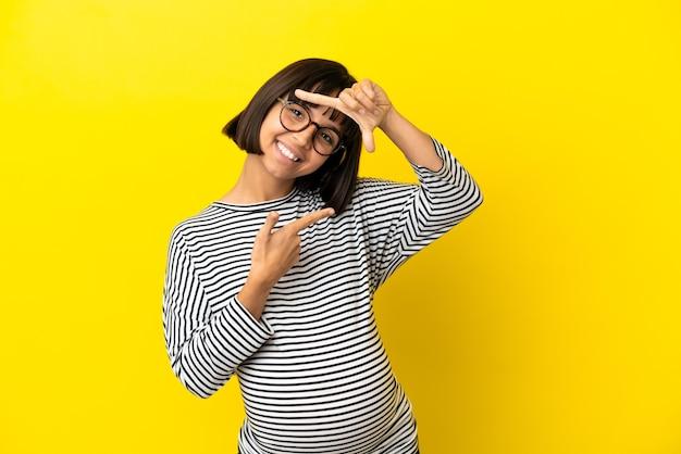 Młoda kobieta w ciąży nad odosobnionym żółtym tłem skupia się twarz. symbol kadrowania