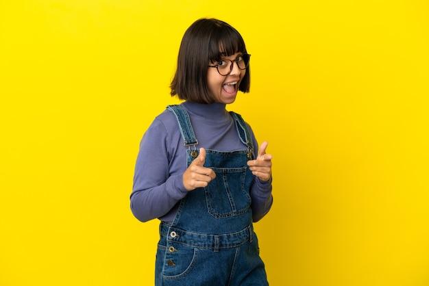 Młoda kobieta w ciąży nad odosobnionym żółtym tłem zaskoczony i wskazujący przód