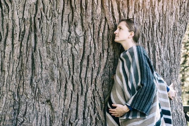 Młoda kobieta w ciąży, opierając się o pień dużego drzewa. zamknięte oczy. jedność z naturą