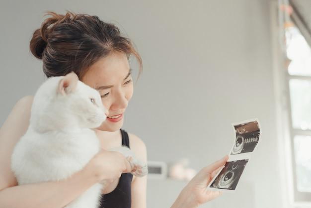 Młoda kobieta w ciąży patrząc na 8 tygodni x-ray usg dziecka