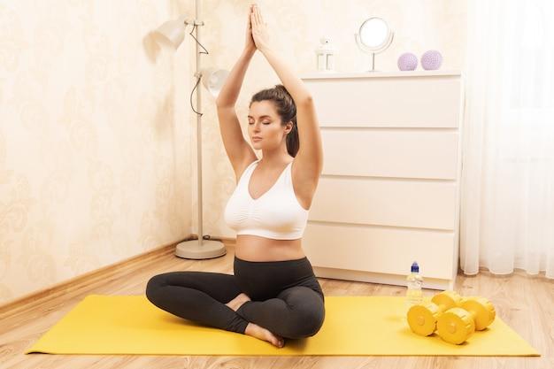 Młoda kobieta w ciąży podczas treningu jogi w domu