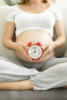 Młoda kobieta w ciąży pozuje z czerwonym budzikiem na kanapie