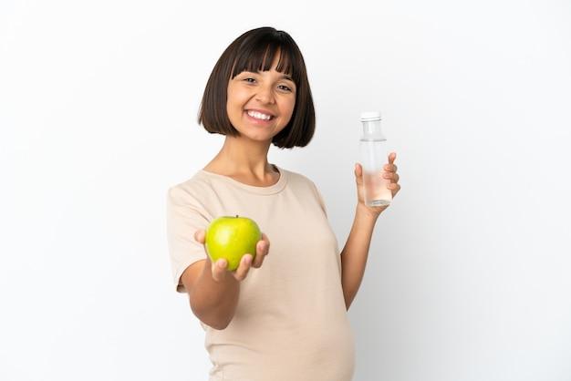 Młoda kobieta w ciąży rasy mieszanej na białym tle z jabłkiem i butelką wody