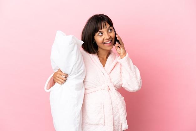 Młoda kobieta w ciąży rasy mieszanej na różowym tle w piżamie i trzymająca poduszkę podczas rozmowy z telefonem komórkowym