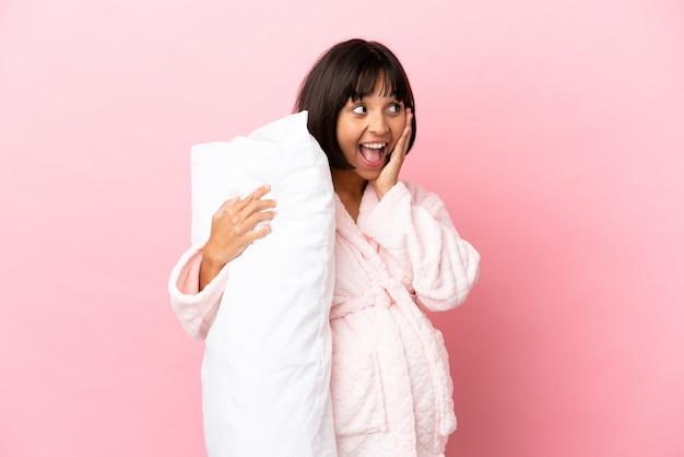 Młoda kobieta w ciąży rasy mieszanej na różowym tle w piżamie i trzymająca poduszkę ze zdziwionym wyrazem twarzy