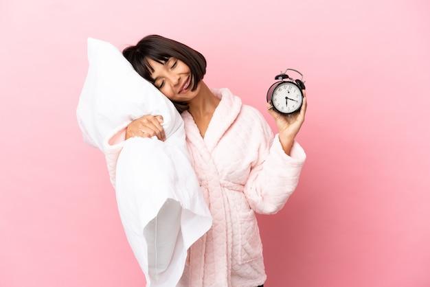 Młoda kobieta w ciąży rasy mieszanej na różowym tle w piżamie i trzymająca zegar i poduszkę ze szczęśliwym wyrazem twarzy