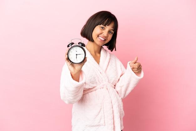 Młoda kobieta w ciąży rasy mieszanej na różowym tle w piżamie i trzymająca zegar z kciukiem do góry