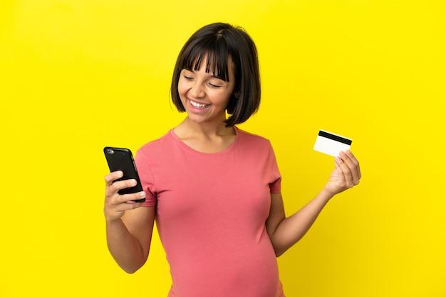 Młoda kobieta w ciąży rasy mieszanej na żółtym tle kupując za pomocą telefonu komórkowego za pomocą karty kredytowej