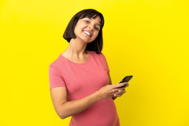 Młoda kobieta w ciąży rasy mieszanej na żółtym tle wysyłająca wiadomość lub e-mail za pomocą telefonu komórkowego