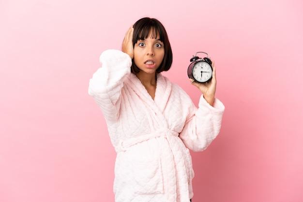 Młoda kobieta w ciąży rasy mieszanej odizolowana na różowym tle w piżamie i trzymająca zegar z zaskoczonym wyrazem twarzy