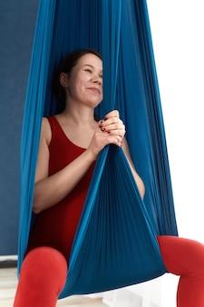 Młoda kobieta w ciąży robi ćwiczenia aerial jogi w hamaku.