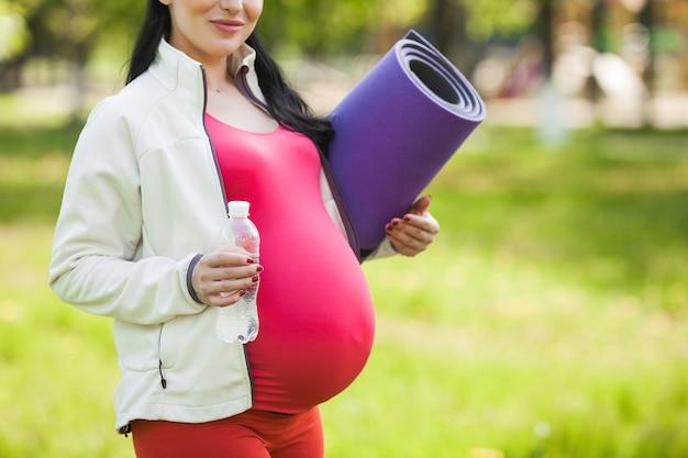 Młoda kobieta w ciąży robi ćwiczenia jogi na świeżym powietrzu w parku.