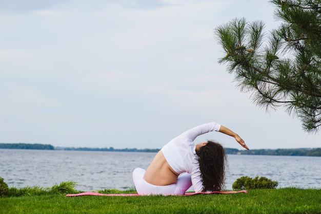 Młoda kobieta w ciąży robi joga na świeżym powietrzu