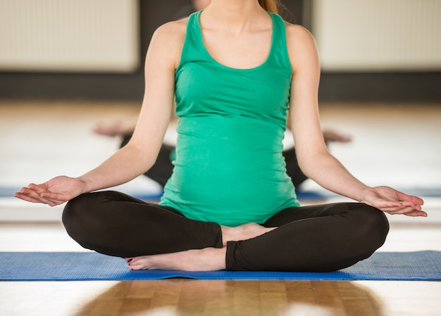 Młoda kobieta w ciąży robi joga.