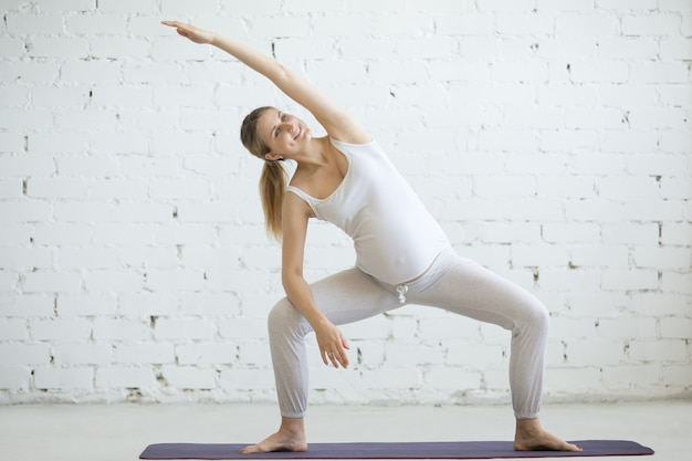 Młoda kobieta w ciąży robi prenatalnej jogi. bogini pozuje z sidebendem