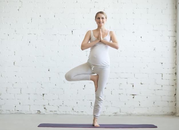 Młoda kobieta w ciąży robi prenatalnej jogi. drzewo stanowi