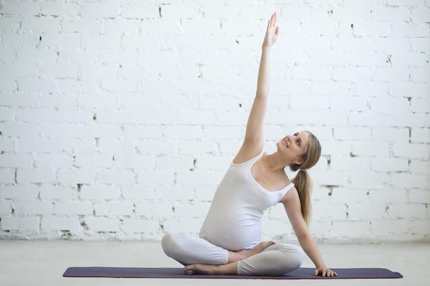 Młoda kobieta w ciąży robi prenatalnej jogi. rozciąganie boczne