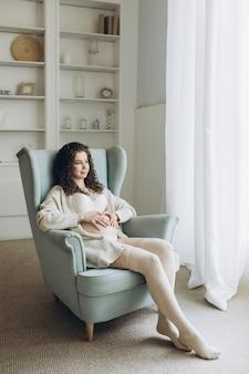 Młoda kobieta w ciąży siedzi na fotelu