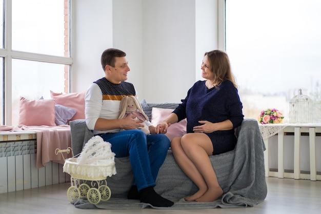 Młoda kobieta w ciąży siedzi przy dużym oknie i tuli ją szczęśliwy mąż. koncepcja młodej rodziny