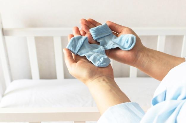 Młoda kobieta w ciąży stoi w pobliżu łóżeczka dziecięcego, trzymając parę niebieskich skarpetek dla noworodka w oczekiwaniu