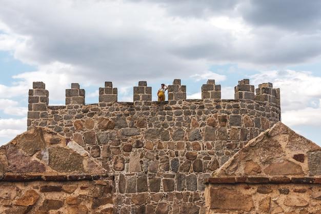 Młoda kobieta w ciąży stojąca na średniowiecznej wieży murów miejskich w avila, hiszpania.
